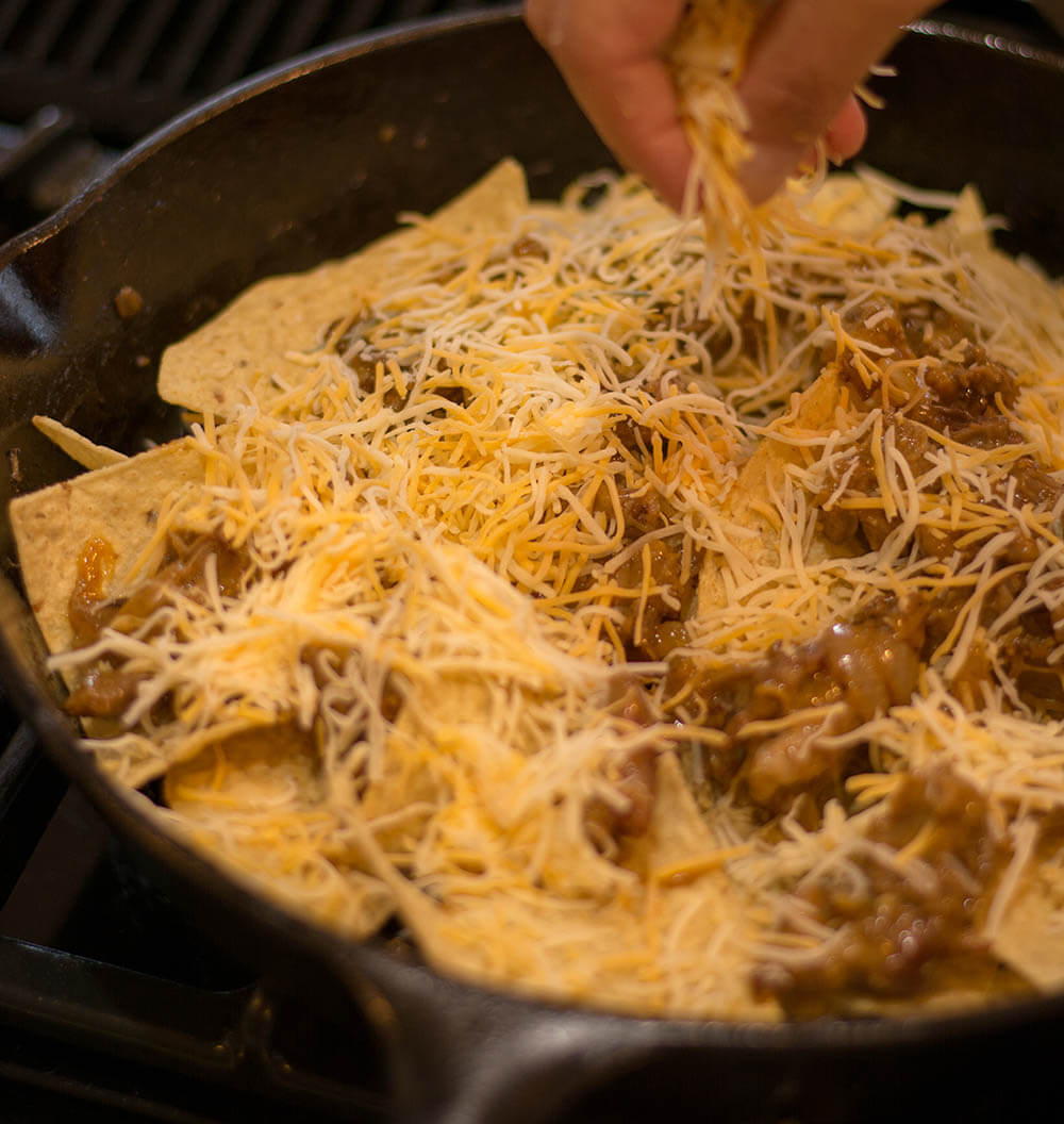 Adding Cheese to Pulled Pork Nachos in a Cast Iron Skillet