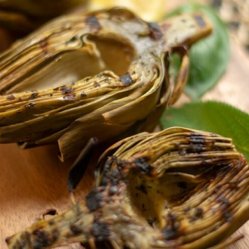 Close up shot of Grilled Artichokes on a Cutting Board with Basil and Sage