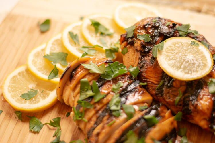 Chicken breasts sliced and topped with flat leaf parsley and lemon slices.