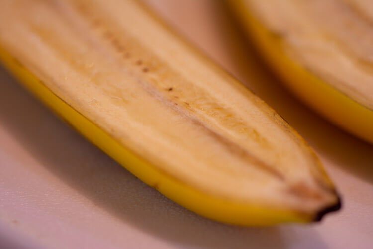 Slice the bananas in half, skin and all