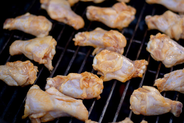 laying the freshly marinated wings on the grill.