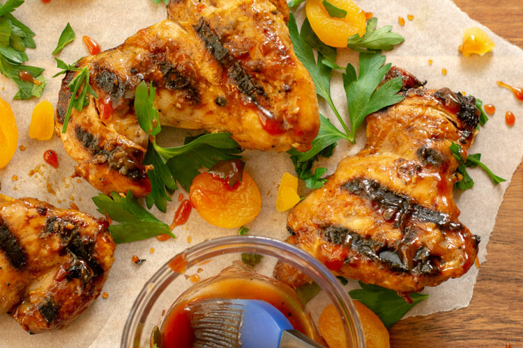 Brushing on some extra Barbecue Sauce on the Apricot Ginger Chicken Thighs
