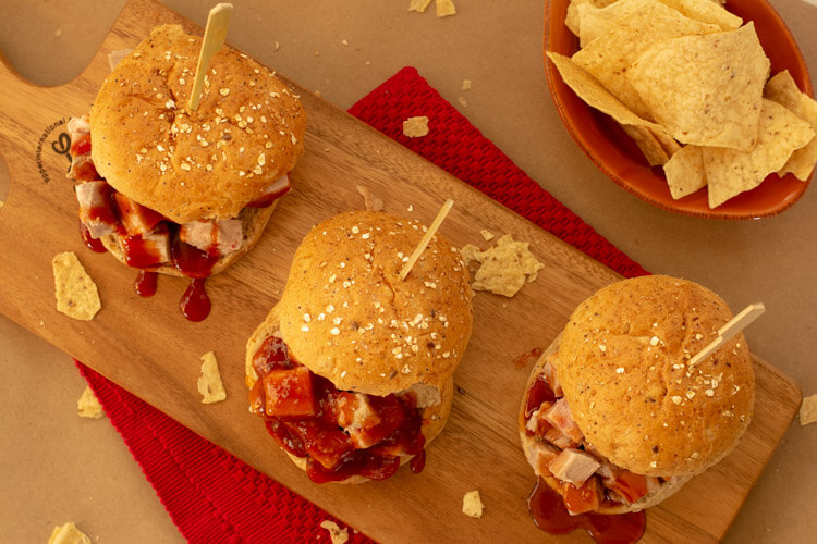 Three Chunky Pulled Pork Sandwiches on a Cutting Board with Corn Chips.