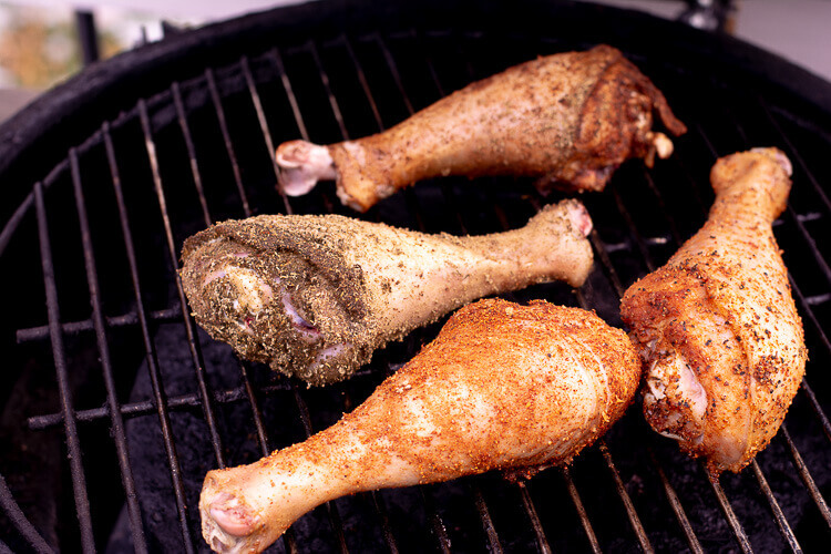 Four turkey legs resting on the grate over indirect heat on the Big Green Egg Charcoal Grill