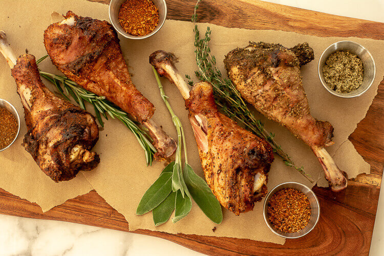 Grilled Turkey Legs on a cutting board with butcher paper and seasoning