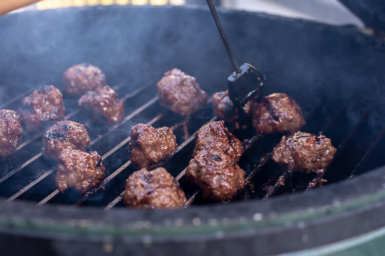 The Big Green Egg Grill with the GrillGrate and Meatballs being brushed with the Asian Chili Sauce