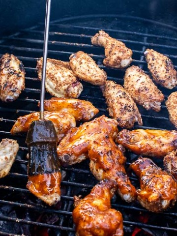 Top down view on the Big Green Egg with the Double IPA Grilled Chicken Wings receiving the basting of the sauce