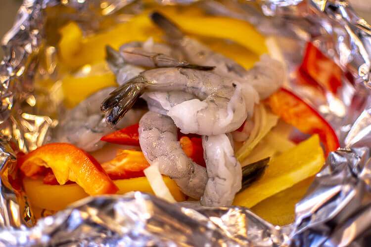 A Double Layer of Foil hold colorful peppers, onions and the peeled shrimp