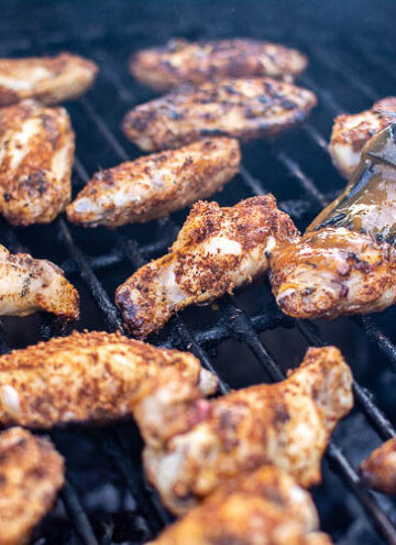 Dry Rubbed Chicken Wings on the Grill being brushed with the Mango BBQ sauce
