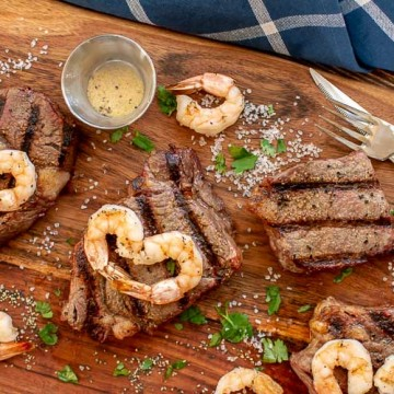 Top down view of cutting board with grilled steak and shrimp. Salt and Parsley are sprinkled around