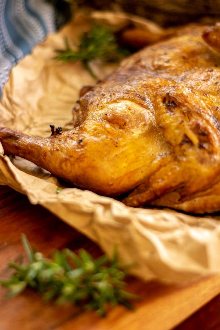 Drumstick is perfectly cooked and is on the butcher paper and cutting board with rosemary in the foreground.