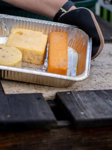 Three large blocks of cheese in a disposable pan on the big green egg table. The cheese is fully smoked and needs to cool