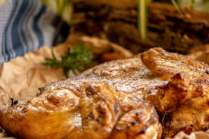 When done, the roasted chicken is sitting on a butcher paper lined baking sheet with herbs in the background