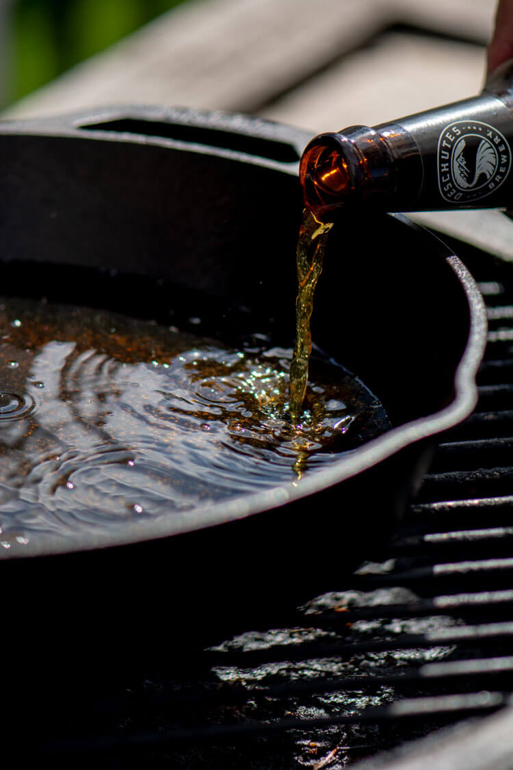 Adding a bottle of beer to the Cast Iron Skillet on Indirect Heat on the grill