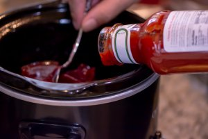 Add a bottle of chili sauce and a can of cranberry to a slow cooker and turn on low