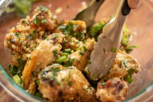bowl of chicken wings topped with fresh cut parsley and green onions