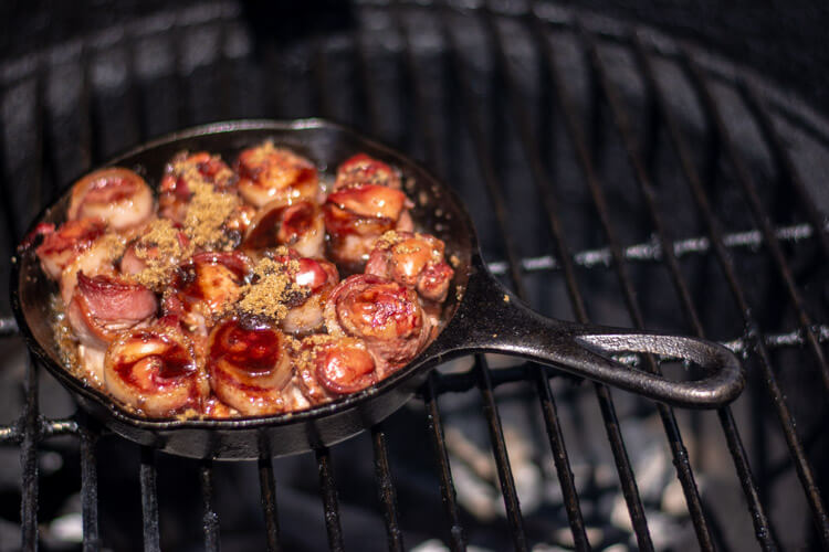 Cast Iron Skillet with two tablespoons of brown sugar sprinkled over the fully cooked bacon wrapped chicken livers
