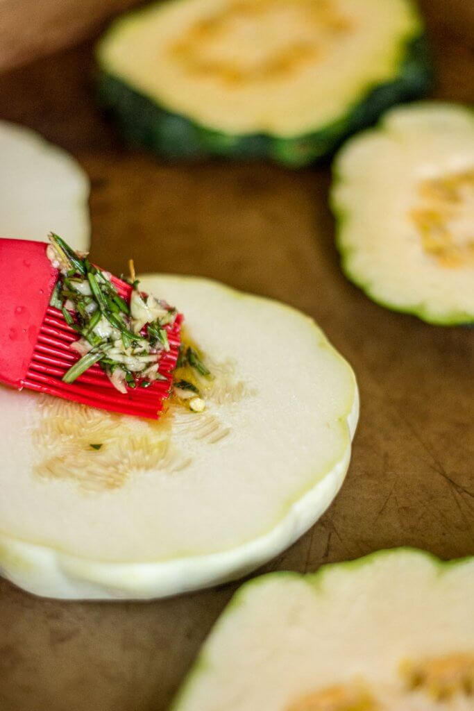 Sliced Pattypan squash being brushed with a garlic and rosemary mixture on a sheet pan
