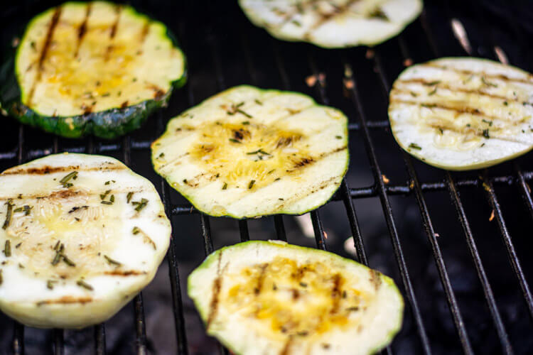 Several Slices of patty pan squash on the grill after being grilled for three to five minutes and turned over. Beautiful grill marks