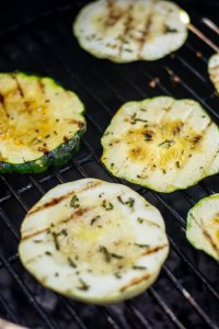 Both green and white squash being grilled on the Big Green Egg with sear marks from the grating