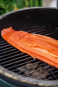 Large Grilled Steelhead fillet laid out on the grating over direct heat on the Big Green Egg