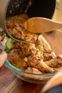 Pouring the garlic parmesan mix on to a pile of wings in a large bowl