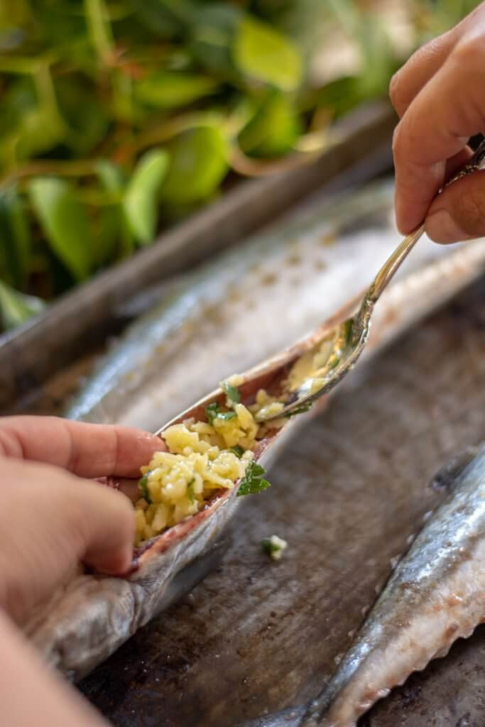 use a spoon to add the garlic mixture to the cleaned spanish mackerel