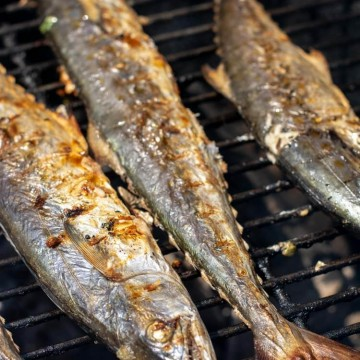 mackerel on the grill after flipping over. With grown grill marks on the skin