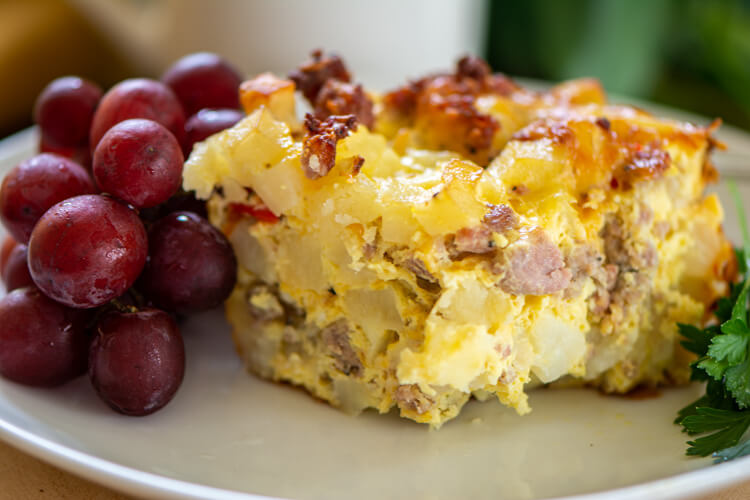 Sliced sausage breakfast casserole on a plate with grapes