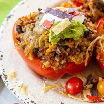 grilled stuffed peppers on a plate with guacamole and chips