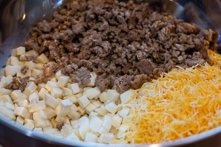 Bowl filled with dry ingredients including the cheese, potatoes and cooked sausage
