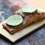 Filet of cooked salmon on a cedar plant with two lime slices on it