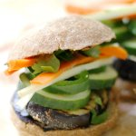 Grilled Eggplant Banh Mi Slider on a roll, topped with cucumbers, peppers, and slices of carrot