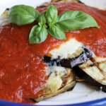 White plate with slices of grilled eggplant under a cheese and marinara sauce and topped with a sprig of fresh basil