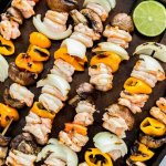 several skewers of shrimp, onions, peppers and mushrooms with a lime on a sheet pan