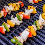 wooden skewers with shrimp and peppers on the grill