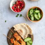 Two skewers of salmon tandoori on a rustic plate with pitas and sliced cucumbers