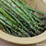 wooden bowl filled with grilled asparagus coasted with balsamic vinegar, garlic and thyme