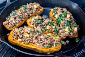 four halves of stuffed squash on a lodge cast iron skillet