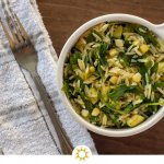 White bowl with a grilled corn orzo pasta salad. Loaded with zucchini and arugula