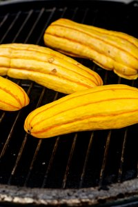 Delicata Squash cut in half and laid face side down on the grill for cooking