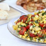 Glass bowl of corn and tomato salad with cilantro and jalapeño for a tex mex grilled side dish