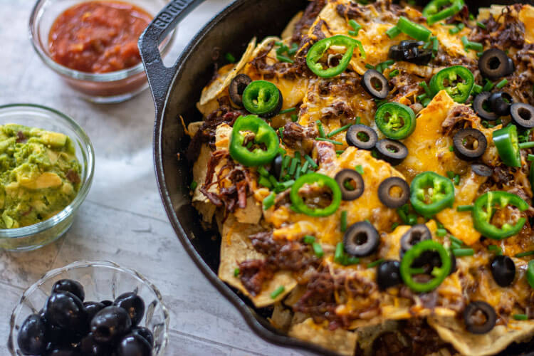 Brisket Nachos topped with jalapeño peppers and black olives with bowls of salsa, guacamole and more olives