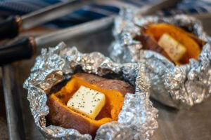 two grilled baked sweet potatoes on a sheet pan read for serving