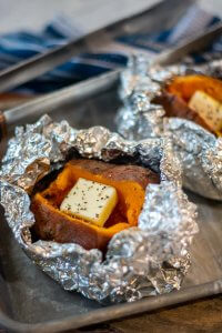 After grilling, the opened foil packets reveal a perfectly grilled baked sweet potato. Added here is some butter.