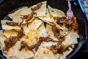 layering the brisket, onion and cheese mixture on tortilla chips in the cast iron skillet