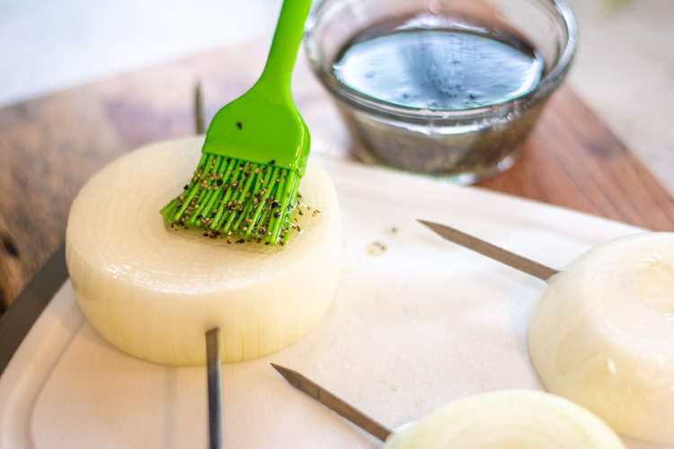 green brush spreading olive oil, salt and pepper on an onion slice on a cutting board