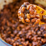 wooden spoon with fully cooked thick baked beans above the dutch oven