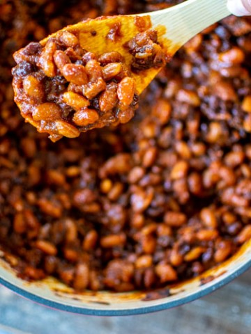 focused on the spoon of thick bourbon baked beans above the dutch oven