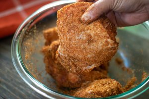 lifting a bone-in chicken thigh from a glass bowl coated in a dry rub